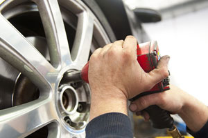 auto repairman worker in automotive industry using an air tool on a tire at auto repair shop